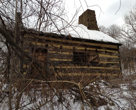 The Neill Log House, photographed through a fence